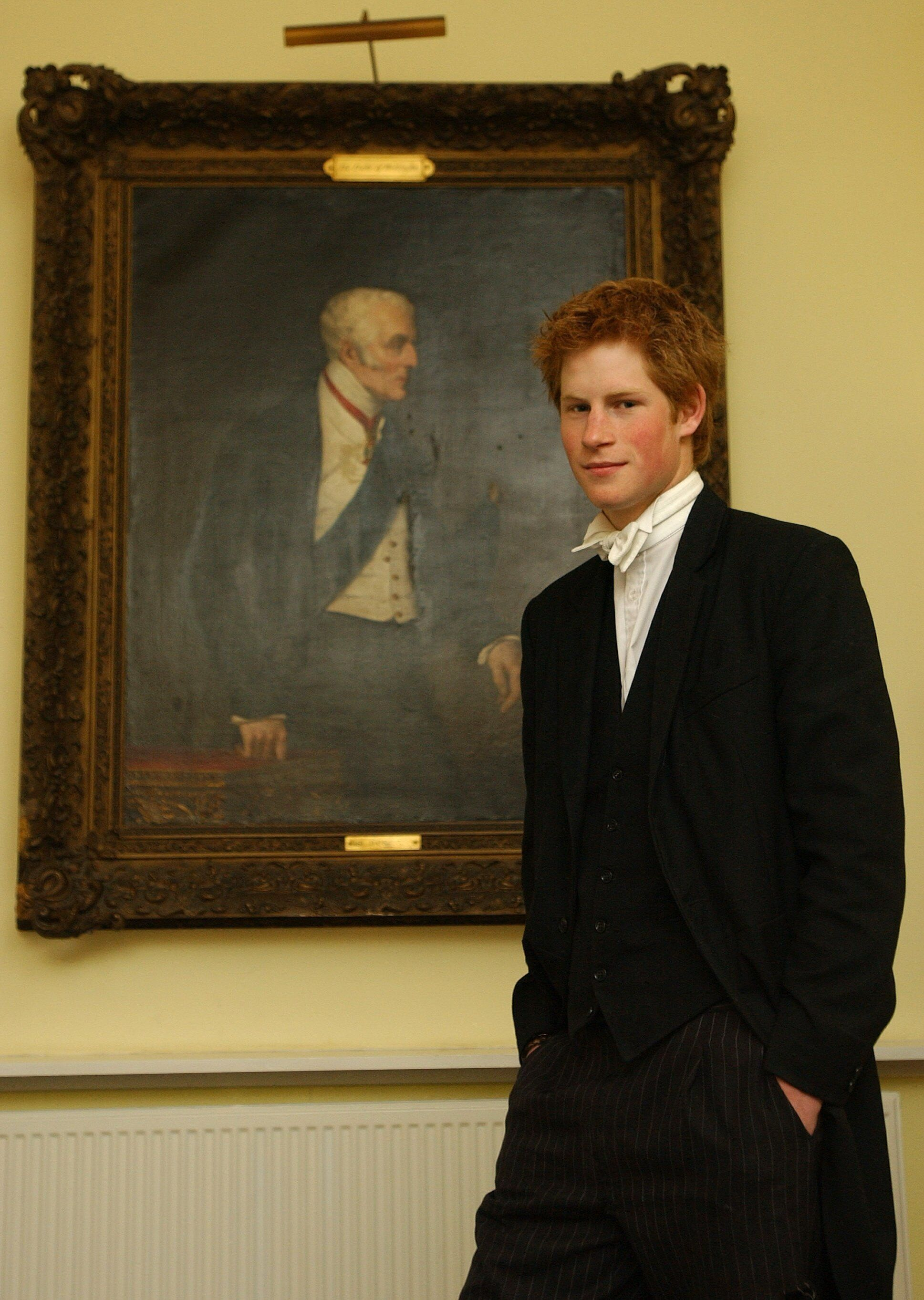 Prince Harry, wearing a school uniform, poses by a portrait of the Duke of Wellington at the Manor House, Eton College, on Ma