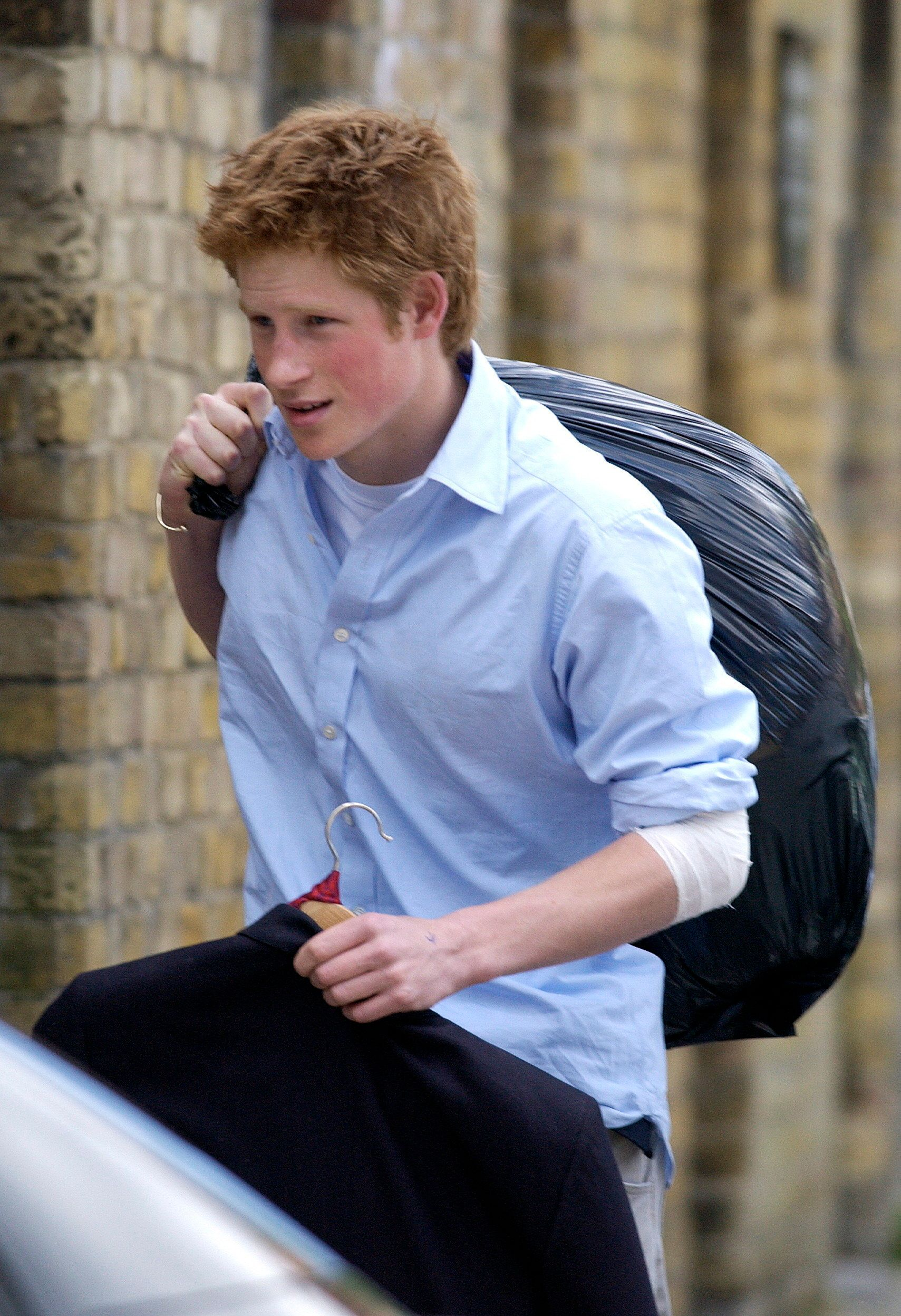 Prince Harry carrying his belongings in a black trash bag on his last day of school at Eton.