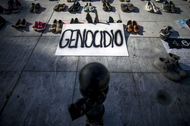 """A sign that says """"genocide"""" in Spanish is displayed next to empty shoes as part of the June 1, 2018, protest outside the Capi"""