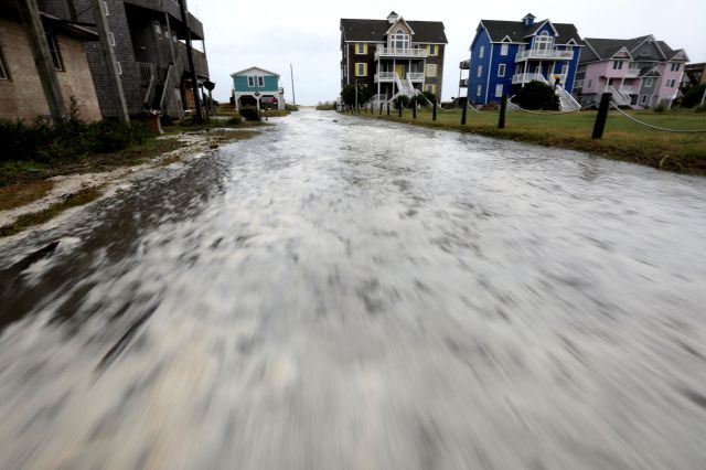 Ocean water rushes down Cape Hatteras Pier Drive in Frisco, North Carolina, as the effects of Hurricane Florence reach the ar