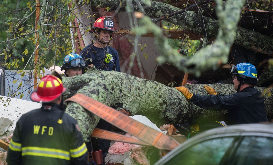 Firefighters work to remove a tree that fell on a house in North Caroline killing a mother and her child on Friday