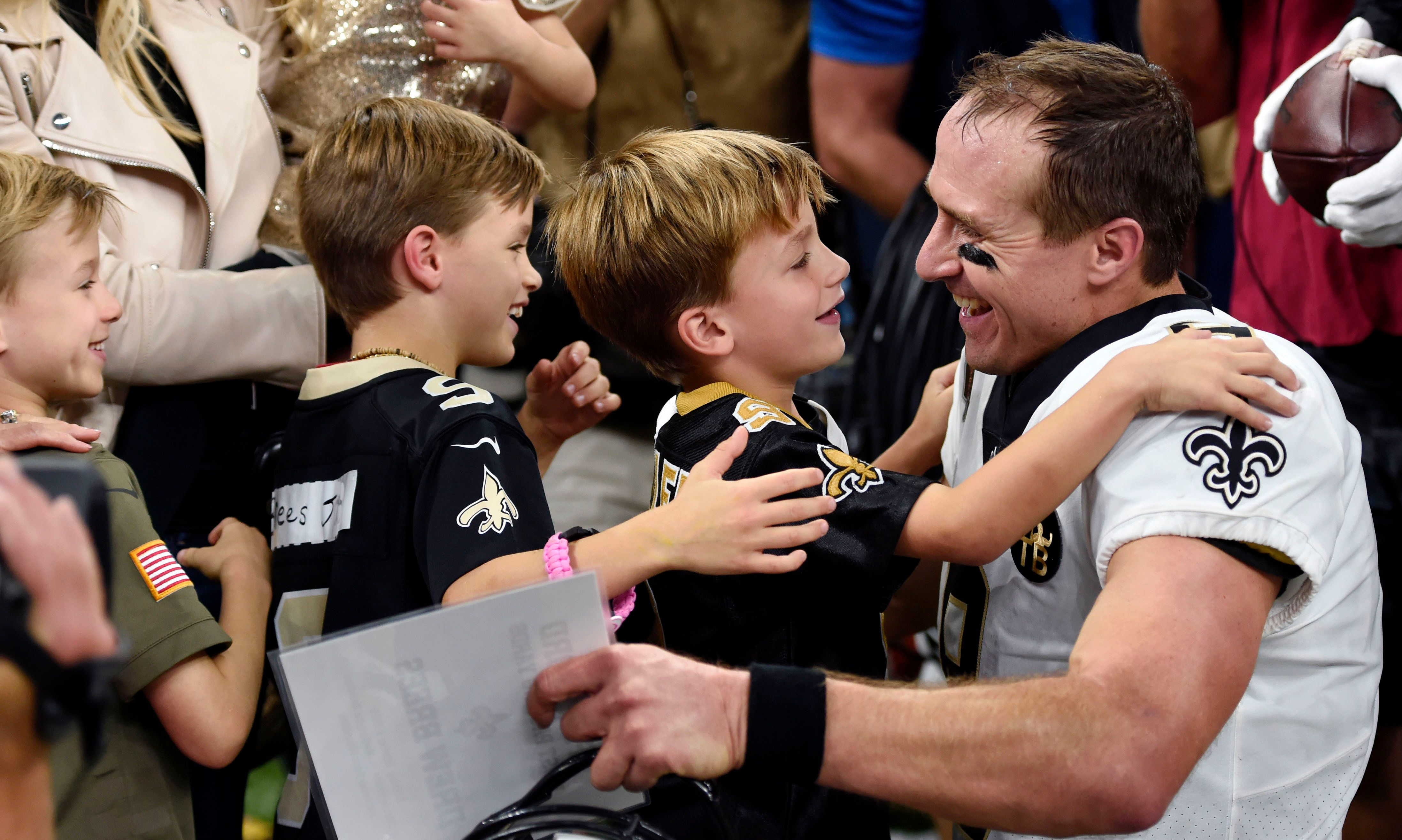 Brees hugs his family after breaking the NFL all-time passing record on Monday night.<i></i>
