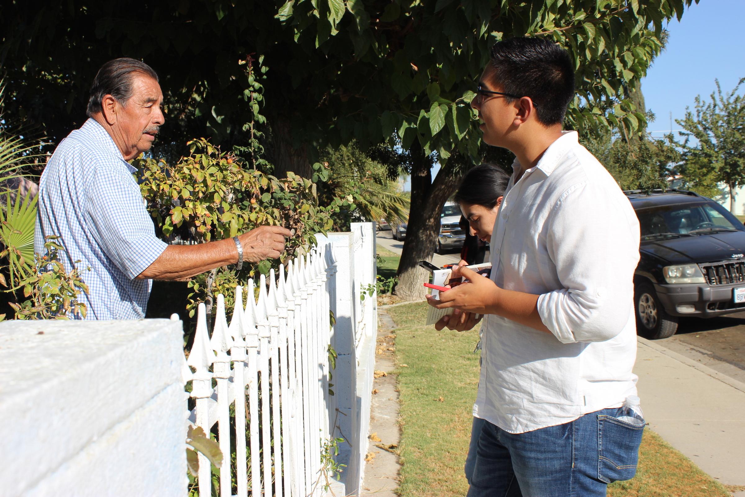 Bryan Osorio, 22, of Delano, talks to an 80-year-old Delano voter. Osorio is a University of California, Berkeley, graduate