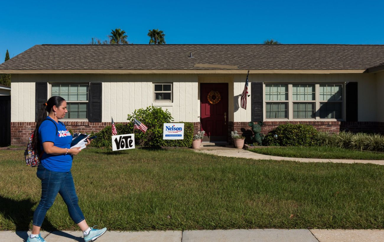 Arleen Sevilla walks by a house with signs supporting Sen. Bill Nelson (D-Fla.) while canvassing in Orlando.