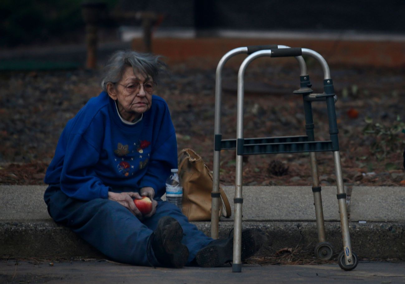 Juanita McLish sits on a curb after she and her husband lost their home in the Campfire blaze raging through Paradise, Calif.