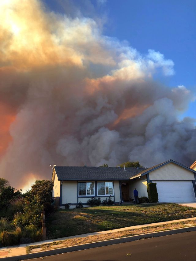 Plumes of smoke loom in the sky several miles away, seen behind a home in Thousand Oaks, Calif., as a wind-driven wildfire kn