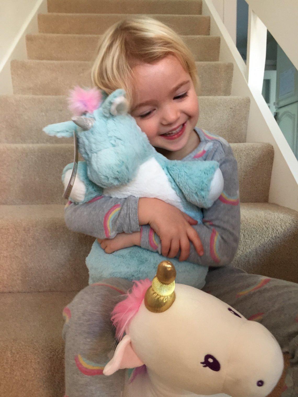 Margo hugs her favourite unicorn toy.