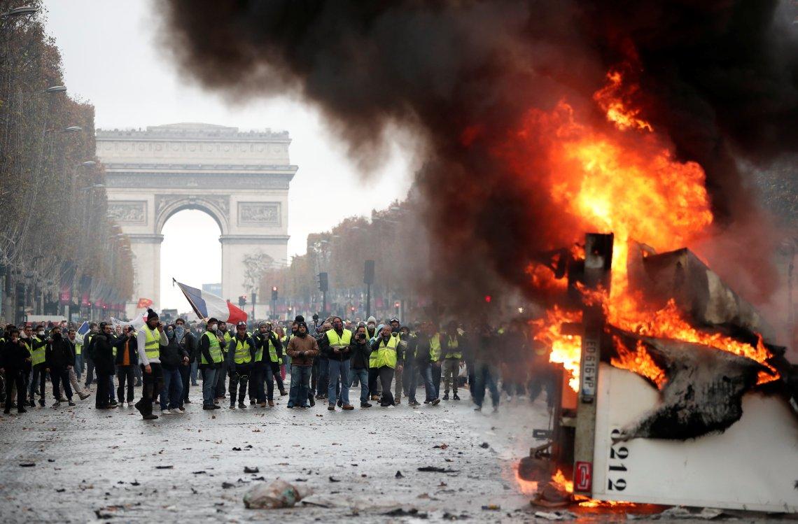An upturned truck ablaze near the Arc de Triomphe