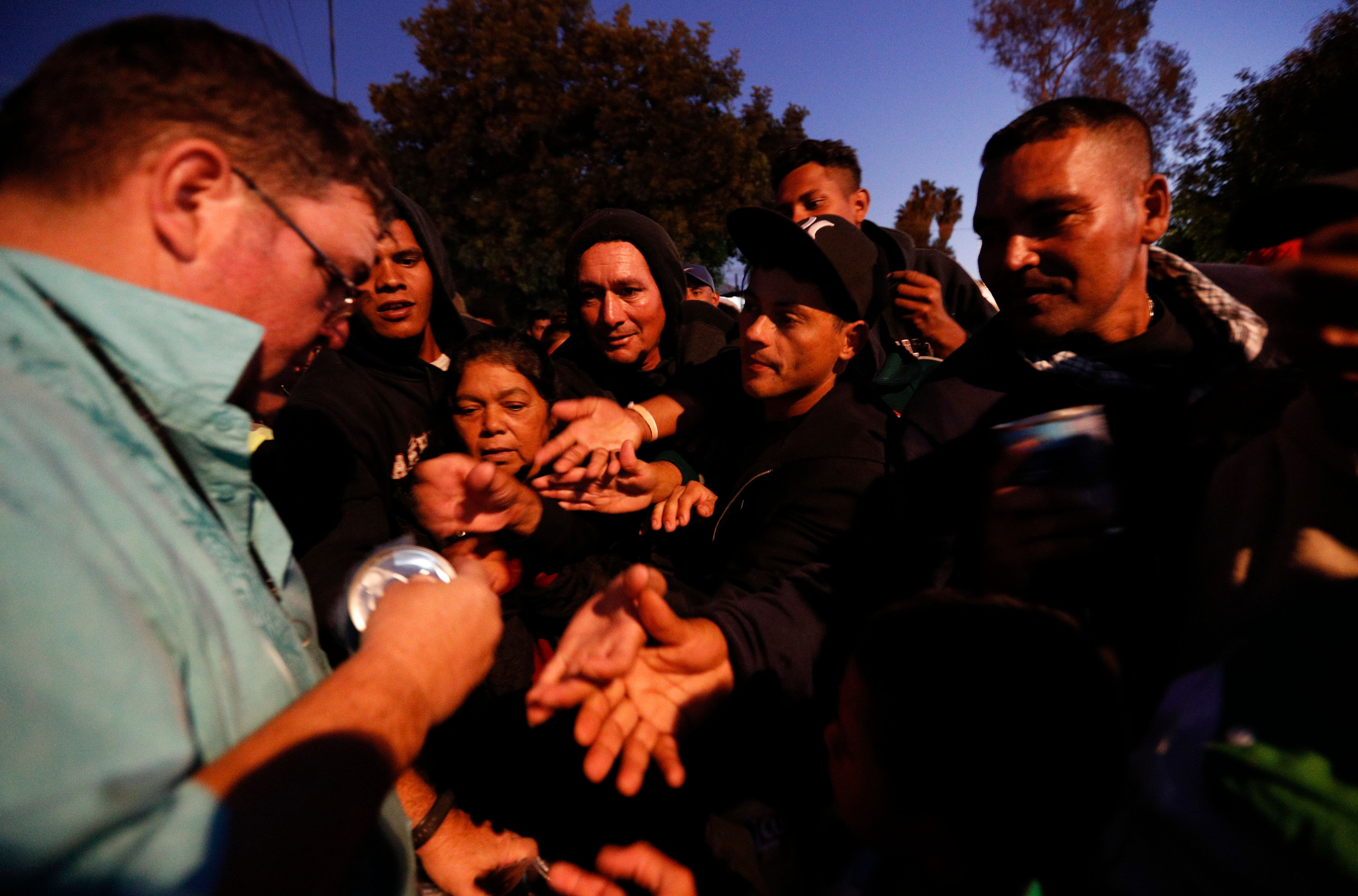 An American well-wisher, left, is swarmed by migrants as he hands out canned soup, adding his efforts to those of many local