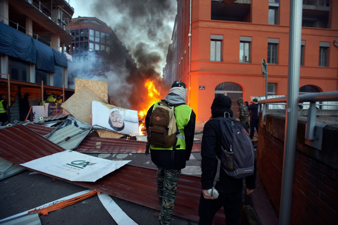 Rioters stand near flames and a barricade on Saturday.