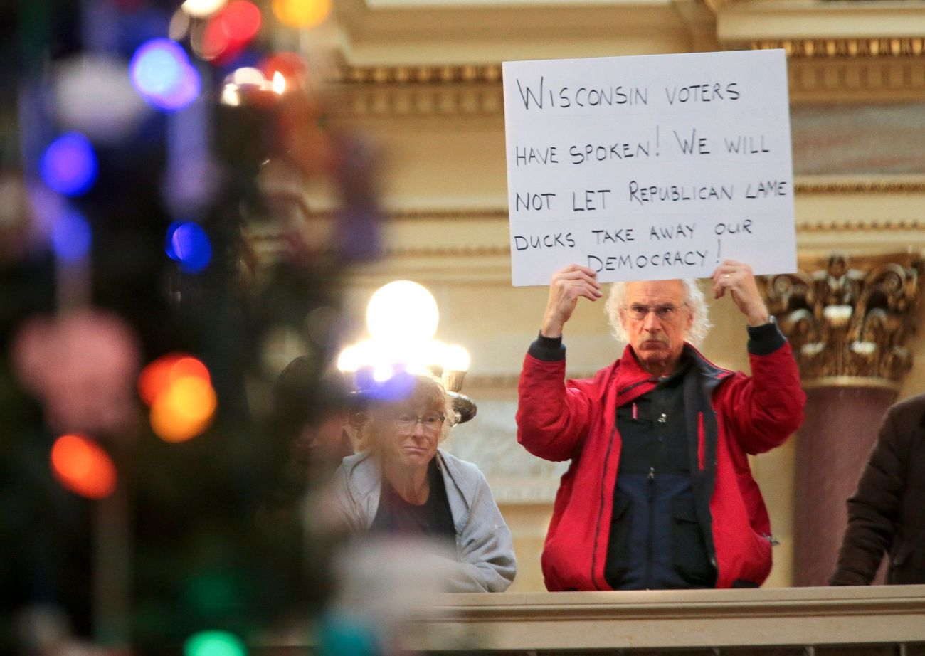 A protestor holds a sign as Wisconsin Republicans strip the incoming Democratic governor of power during the 2018 lame duck s
