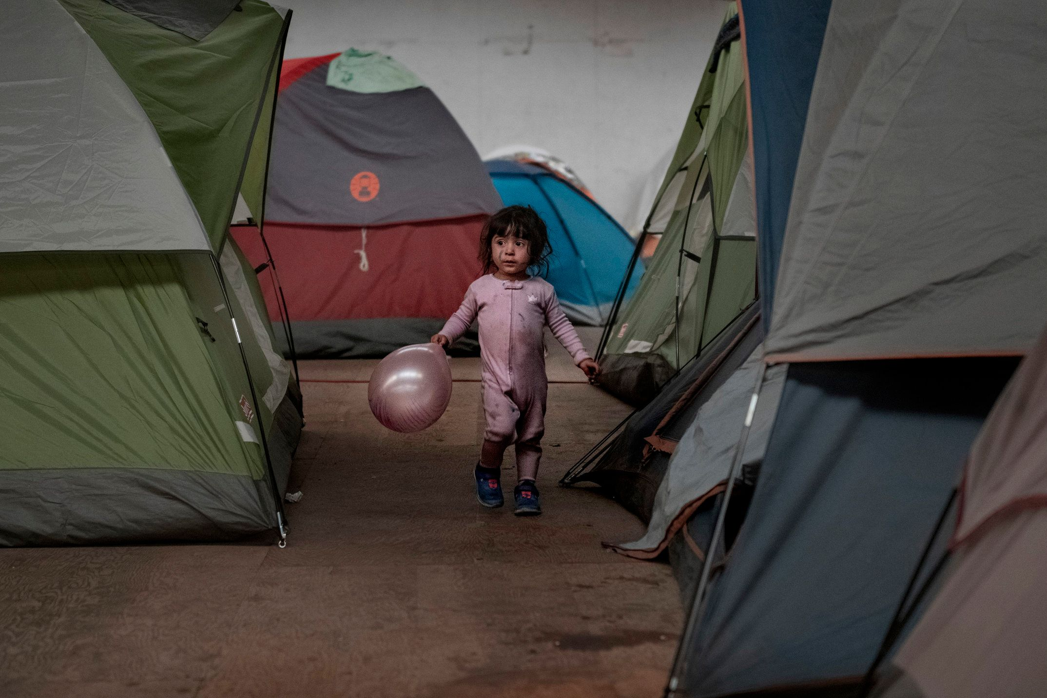 A girl holds walks among tents inside an empty warehouse used as a shelter set up for migrants in downtown Tijuana, Mexico.