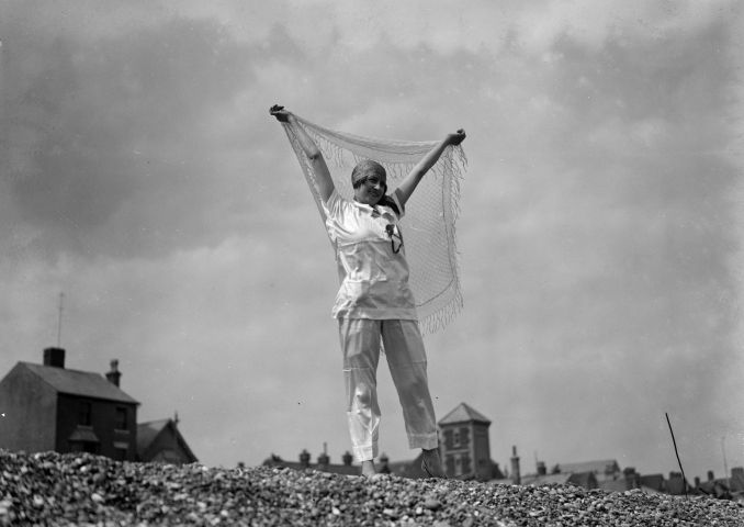 A woman wearing her beach pajamas on a beach in England, dated 1927.