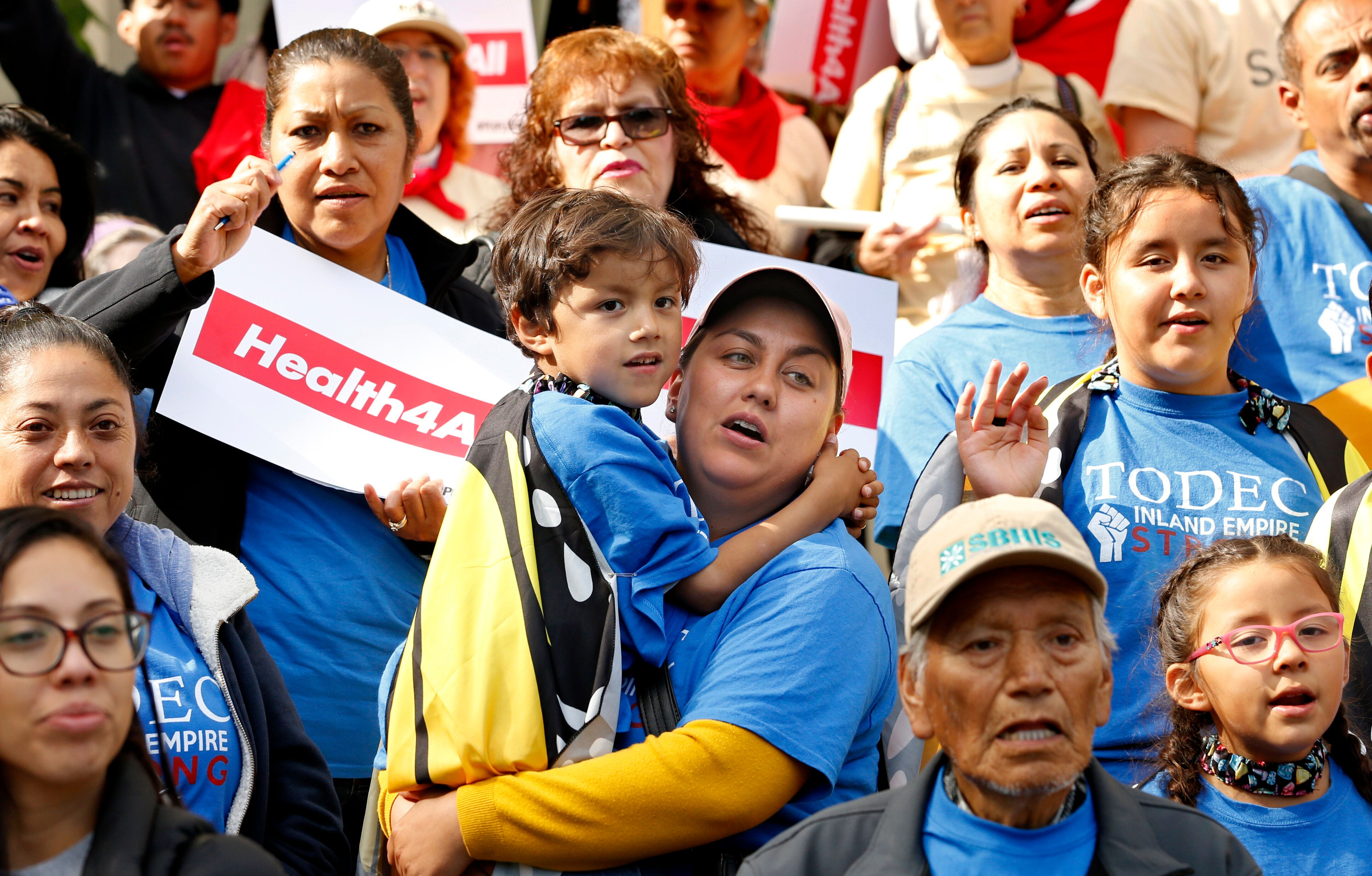 Oralia Sandoval, center, holds her son Benjamin, 6, as she participates in an Immigrants Day of Action rally, Monday, May 20,