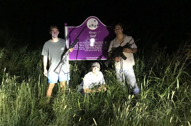 Ole Miss students Ben LeClere, John Lowe and Howell Logan pose with guns by a bullet-riddled plaque marking the place where E