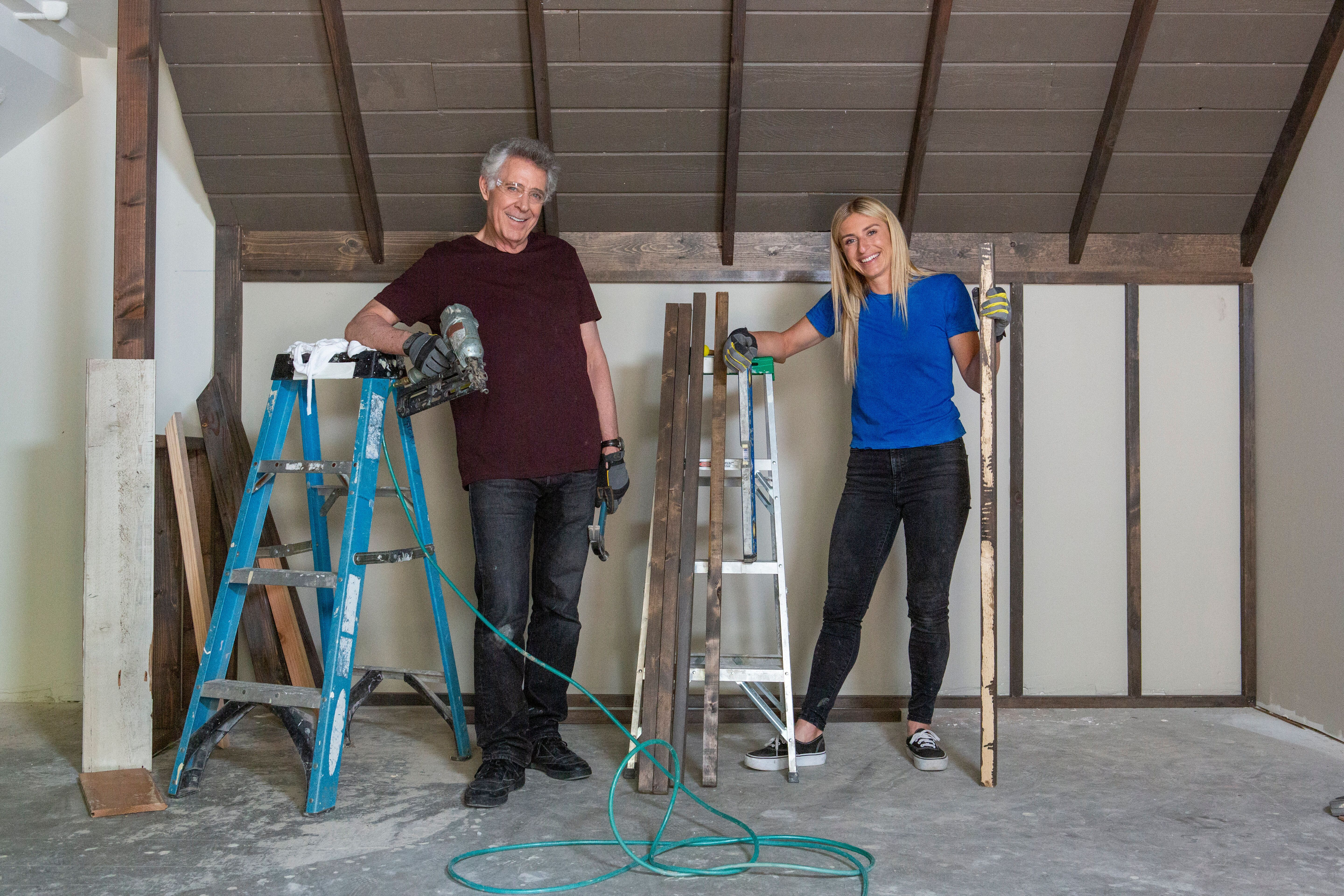 Barry Williams (Greg) and host Jasmine Roth pose after installing old wood planks, salvaged from the basement, to recreate th
