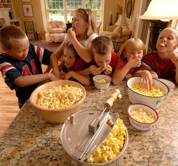 A group of children devour their popcorn in a promotional image used by Whirley Pop.