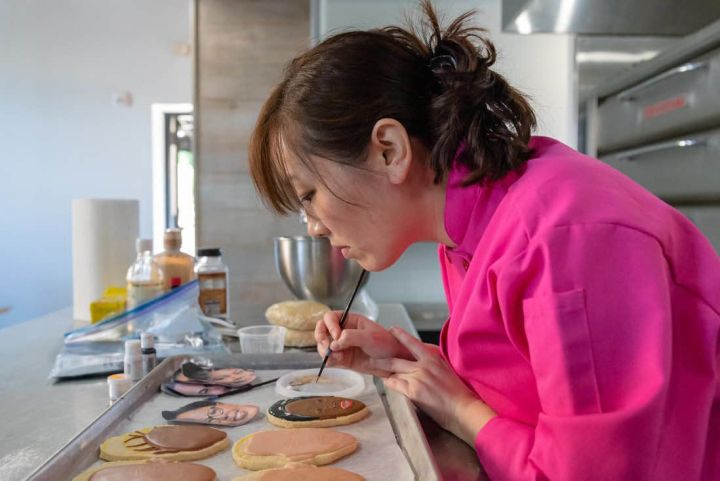 "Jasmine Cho works on a cookie. (Photo by <a href=""https://www.katebuckleyphotography.com/"" target=""_blank"" rel=""noopener noreferrer"">Kate Buckley</a>)"