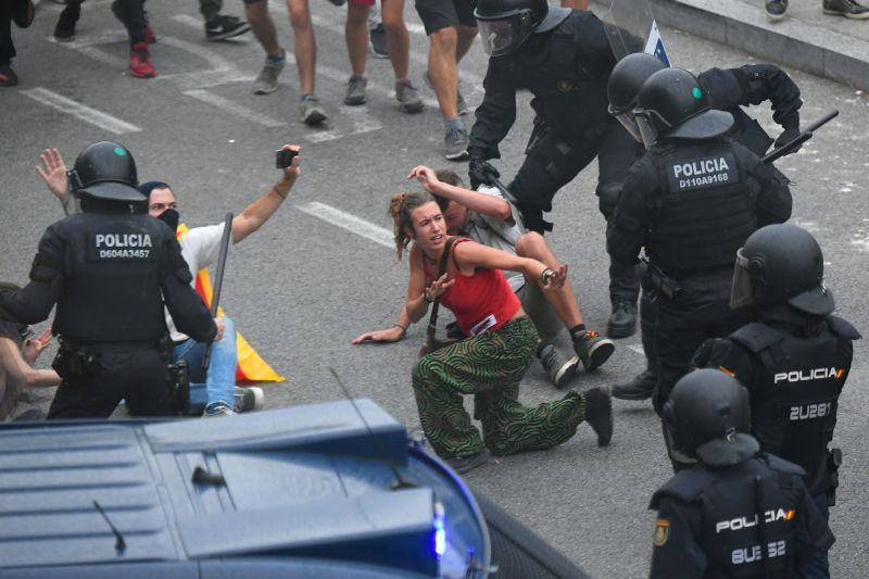 Protesters clash with Spanish policemen outside El Prat airport in Barcelona on October 14, 2019 as thousands of angry protesters took to the streets after Spain's Supreme Court sentenced nine Catalan separatist leaders to between nine and 13 years in jail for sedition over the failed 2017 independence bid. - As the news broke, demonstrators turned out en masse, blocking streets in Barcelona and elsewhere as police braced for what activists said would be a mass response of civil disobedience. (Photo by LLUIS GENE / AFP) (Photo by LLUIS GENE/AFP via Getty Images)