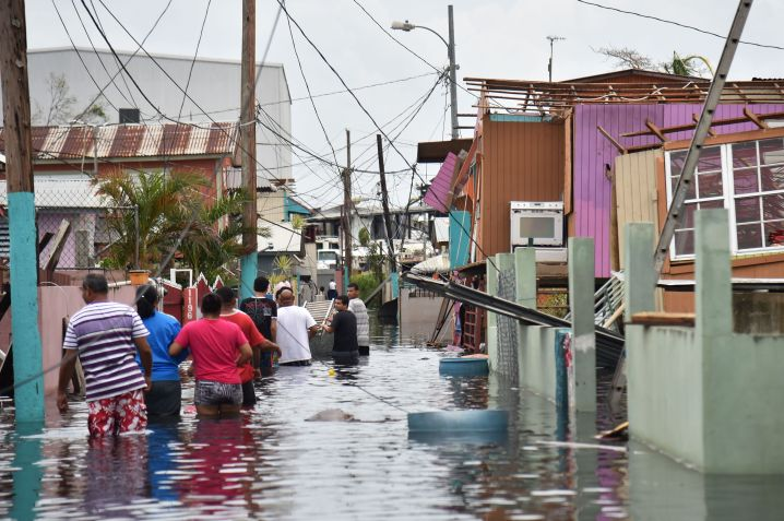 People walk in a flooded street next to damaged houses in Puerto Rico on Sept. 21, 2017, after Hurricane Maria hit.