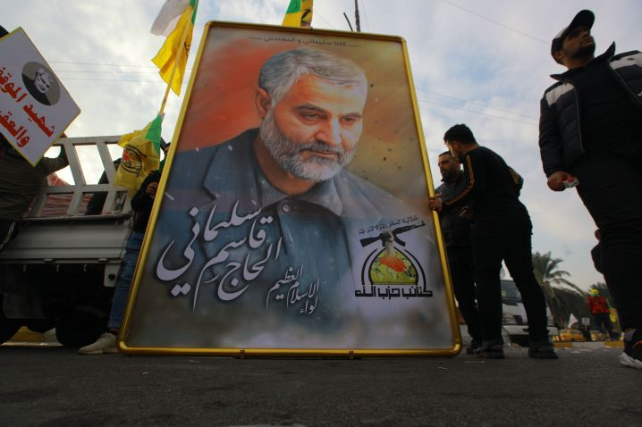 Mourners stand next to a giant portrait for Qassem Soleimani during a funeral procession.