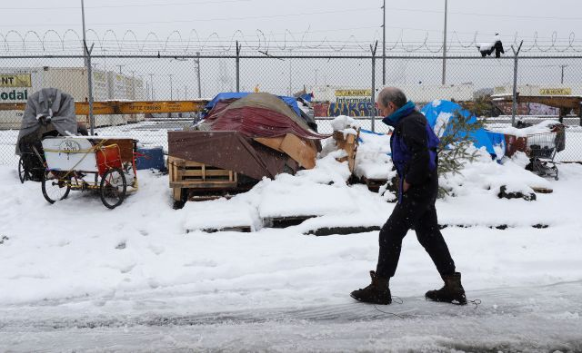 Kevin Shepherd walks back to the tent where he lives as snow falls in Seattle on Feb. 11, 2019. Shepherd, who works as a musi