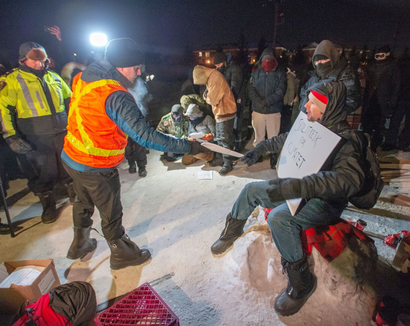 Police serve an injunction to protesters at a rail blockade in St-Lambert, south of Montreal, Que. on Thursday.