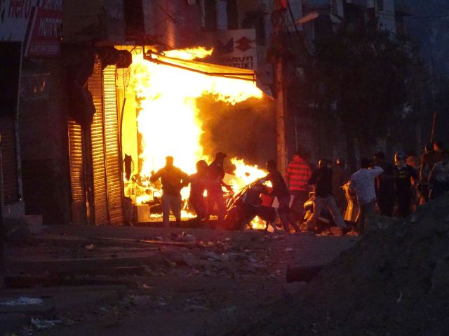 A shop burns as a mob sets it on fire during violence between two groups in New Delhi, India, on Feb. 25, 2020.