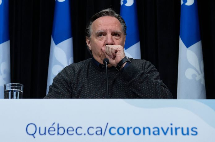 The Premier of Quebec, François Legault, coughs in his hand as he speaks during a press conference on the COVID-19 ...