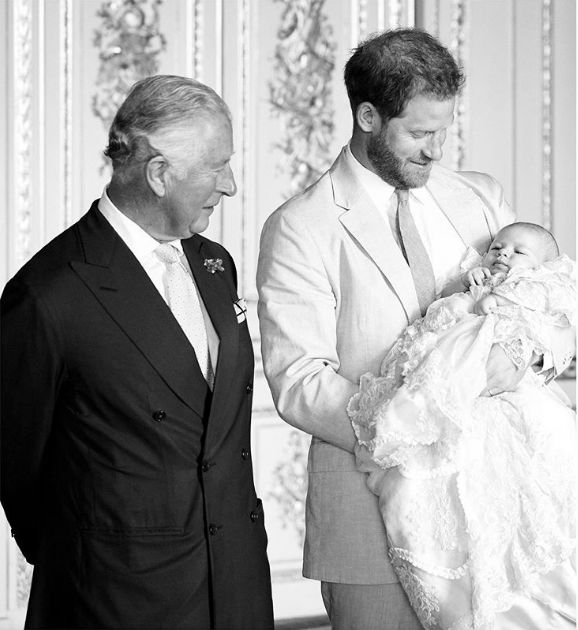 Prince Charles and Harry look at Archie on the day of his christening.