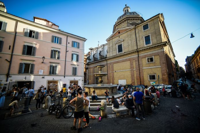 People drink in a square in Rome on May 21, 2020, despite government warnings that people should continue to respect social d