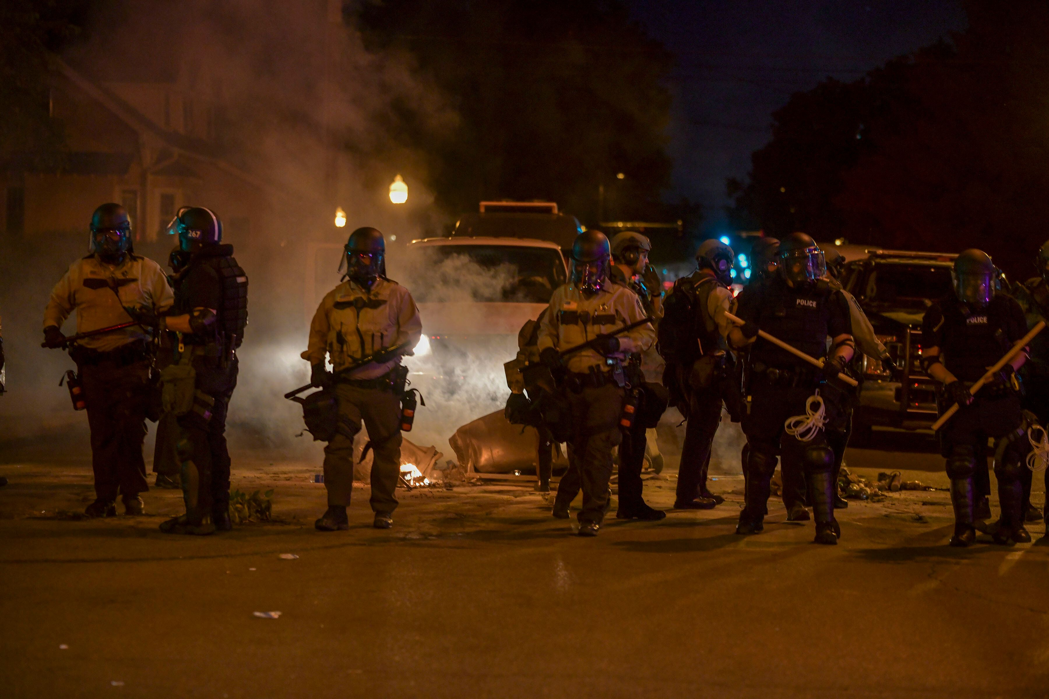 Police are seen armed with batons after protesters violated a curfew in effect in Minneapolis on Saturday.