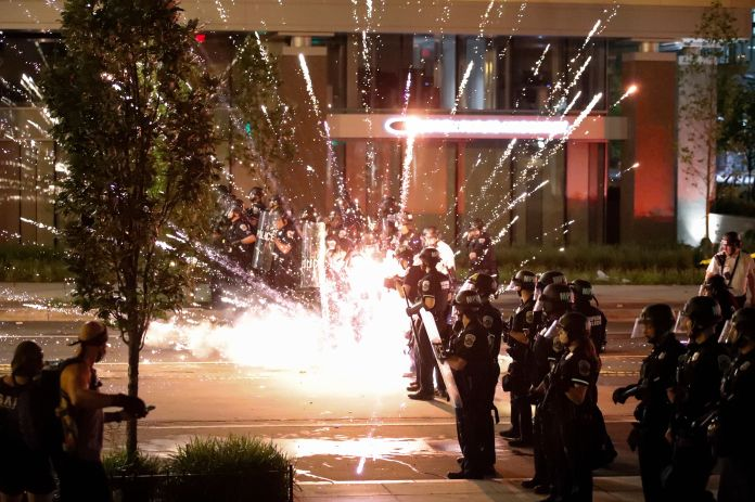 A firework explodes by a police line as demonstrators gather to protest the death of George Floyd.