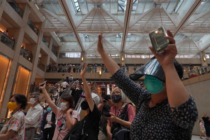"Protesters gesture with five fingers, signifying the ""Five demands - not one less"" in a shopping mall during a protest agains"