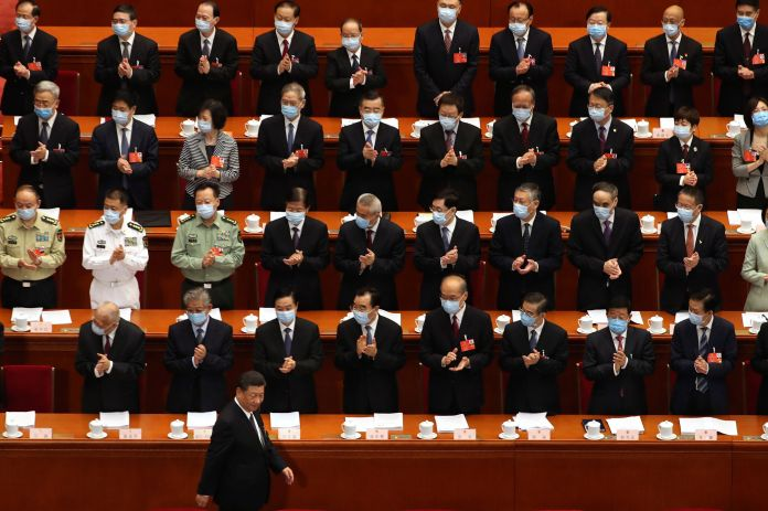 Delegates applaud as Chinese President Xi Jinping arrives for the opening session of China's National People's Congress (NPC)