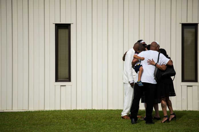 A group of people exiting a memorial for Floyd embrace each other outside the R.L. Douglas Cape Fear Center on June 6.