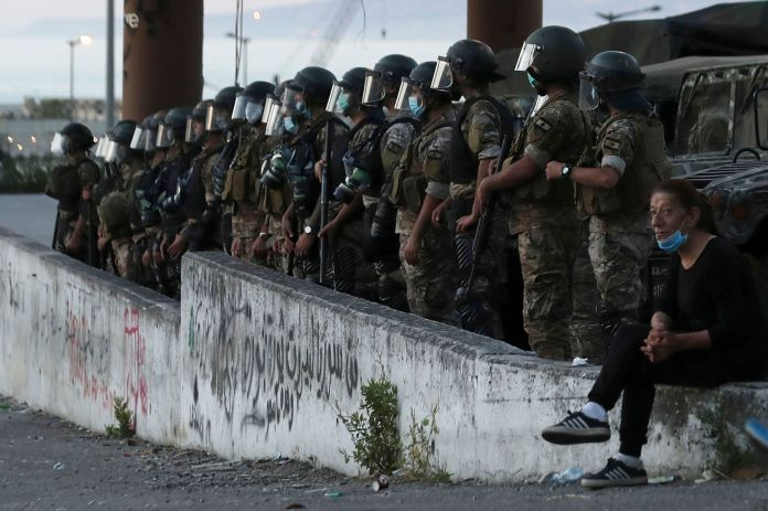 An anti-government protester, right, sits near Lebanese army soldiers standing guard in Beirut, Lebanon, Saturday, June 13, 2