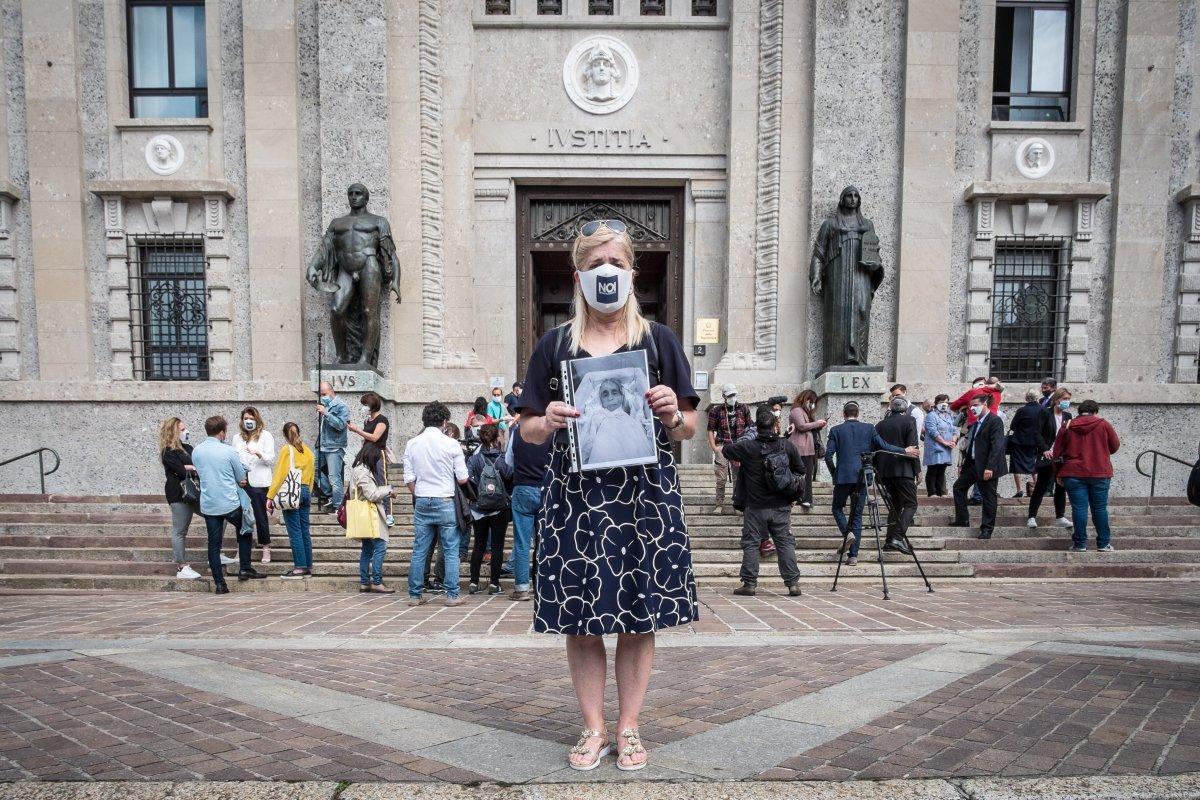 Laura Capella muestra una foto de su padre, fallecido por covid-19, frente a la Fiscalía de Bérgamo...