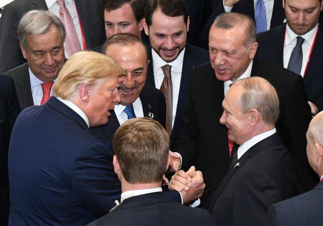 President Donald Trump shakes hands with Russian President Vladimir Putin as Turkey's President Recep Tayyip Erdogan (second