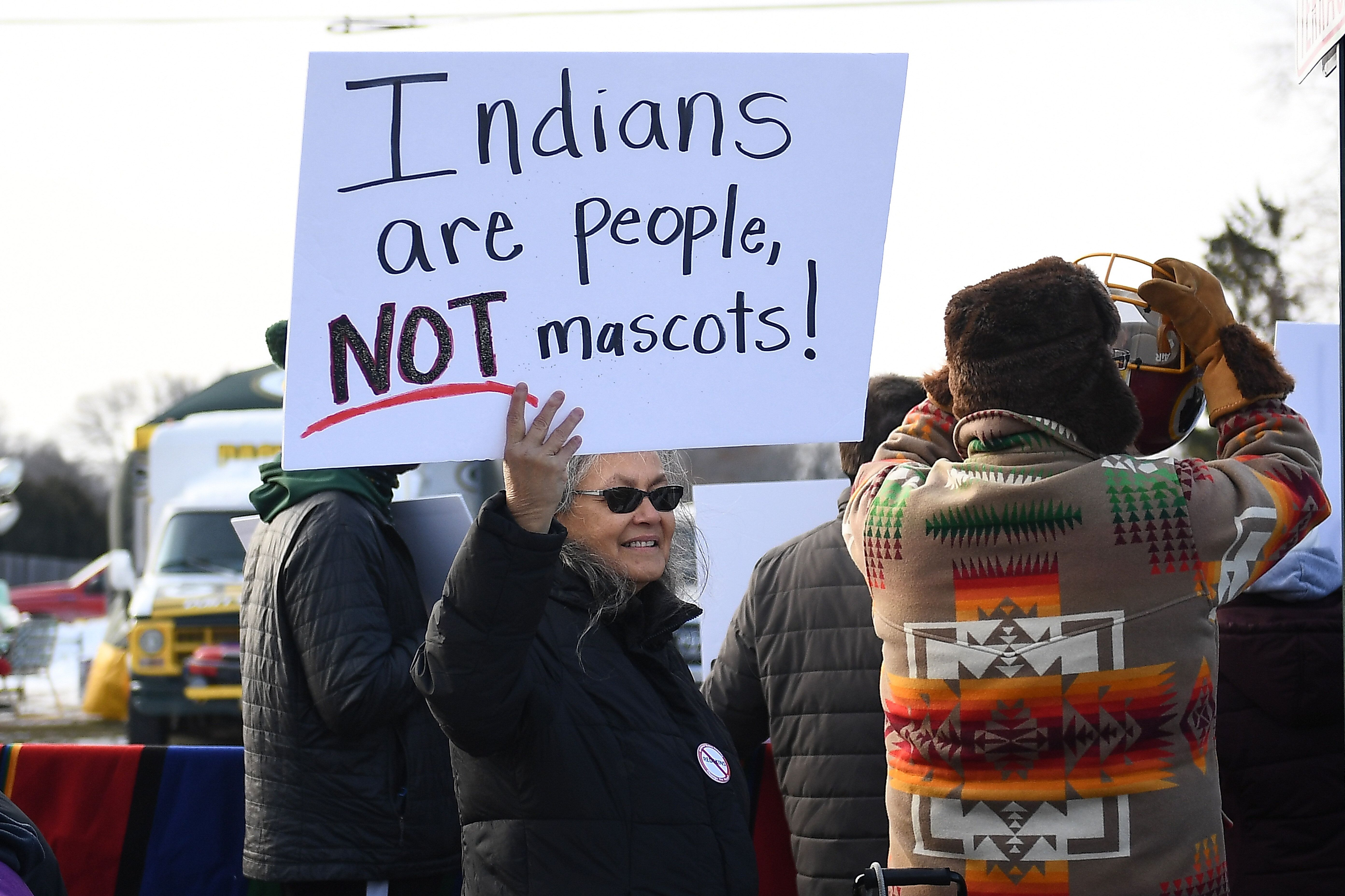 A woman demonstrates against the Washington team name outside a game in Green Bay, Wisconsin, in 2019. The franchise has ofte
