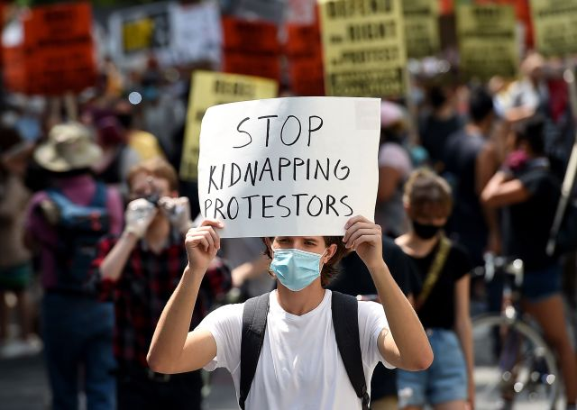 """Demonstrators participate July 25 in a rally against """"Trump's Police State"""" in Washington, D.C."""