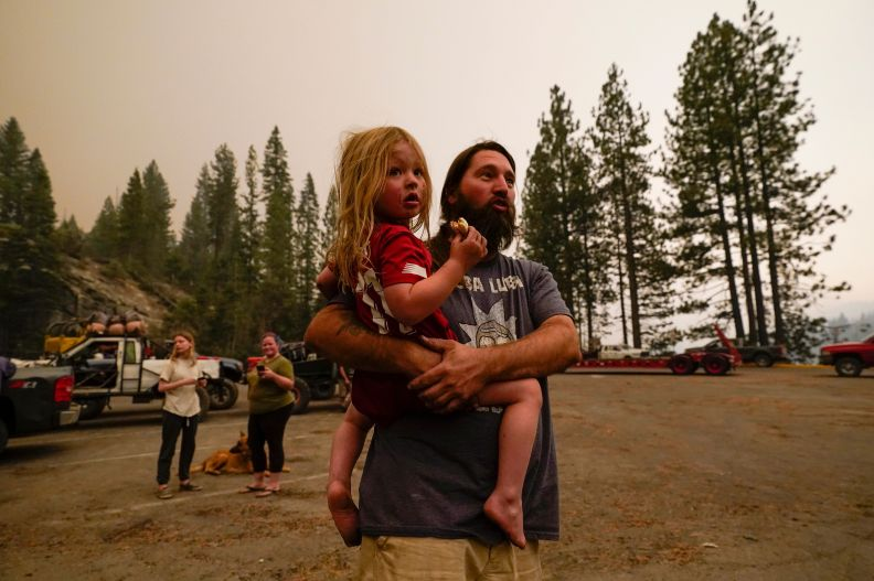 Jeremy Hedrick holds his son Jeep as smoke from the Creek Fire fills the air on Monday.