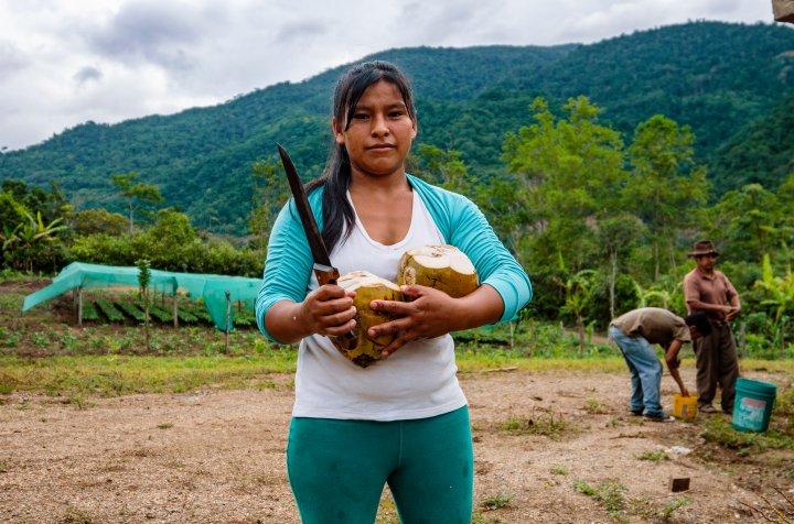 Une agricultrice péruvienne sur ses terres, tenant une noix de coco fraîche dans ses bras.