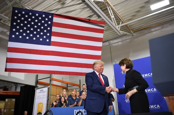 President Donald Trump greets then-Lockheed Martin CEO Marillyn Hewson at the Derco Aerospace Inc. plant in Milwaukee on July