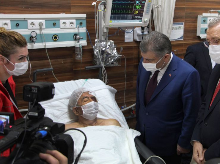 Turkey's Health Minister Fahrettin Koca, right, visits Ahmet Citim, rescued from the debris of his collapsed house, in Izmir,