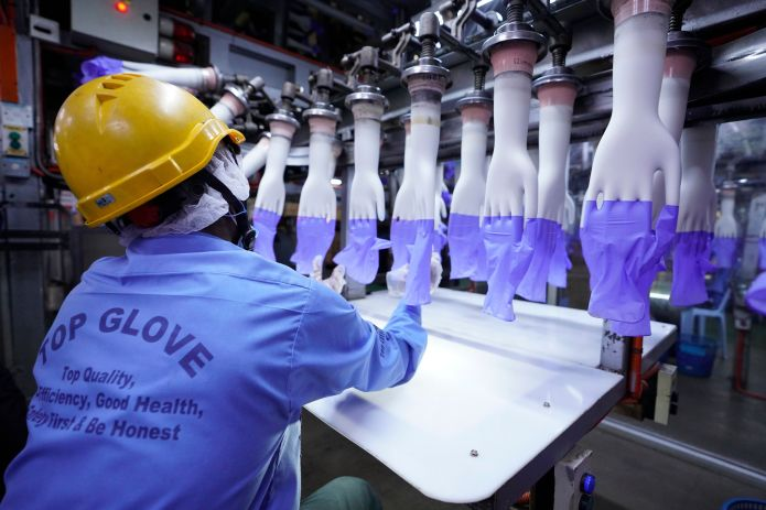 In this Aug. 26 file photo, a worker inspects disposable gloves at the Top Glove factory in Shah Alam on the outskirts of Kua