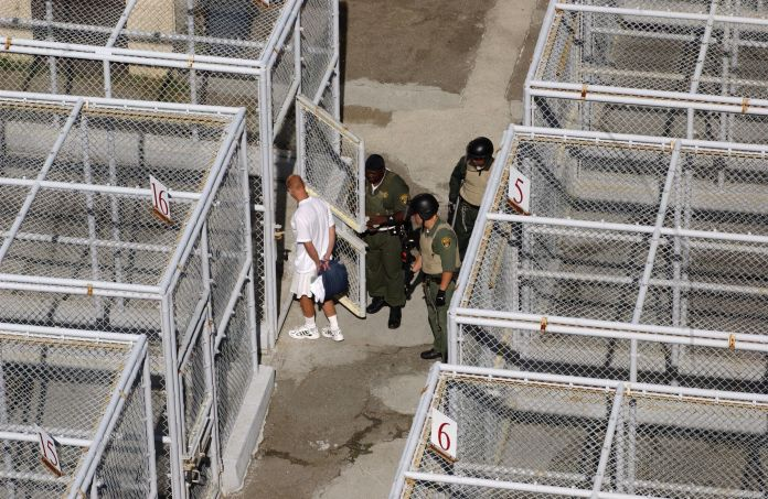 A guard at San Quentin prison is seen checking doors of cells housing death row inmates. At least 158 claims were filed in Ca