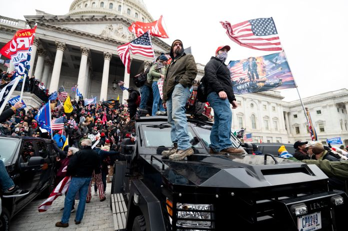 Trump supporters stand on U.S. Capitol Police armored vehicles as others take over the steps of the Capitol on Jan. 6, 2021.