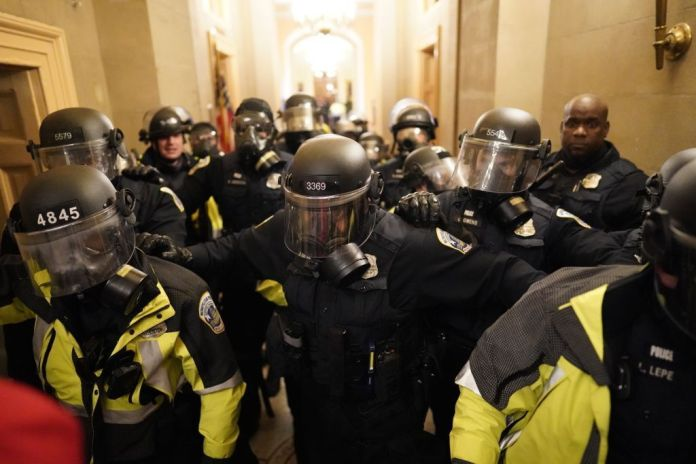Riot police clear the hallway inside the Capitol on Jan. 6, 2021.