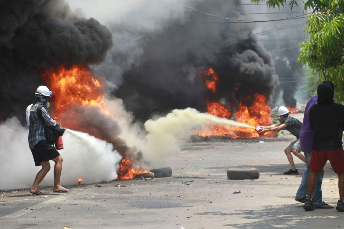 Anti-coup protesters extinguish fires during a protest in Thaketa township Yangon, Myanmar, Saturday, March 27, 2021.